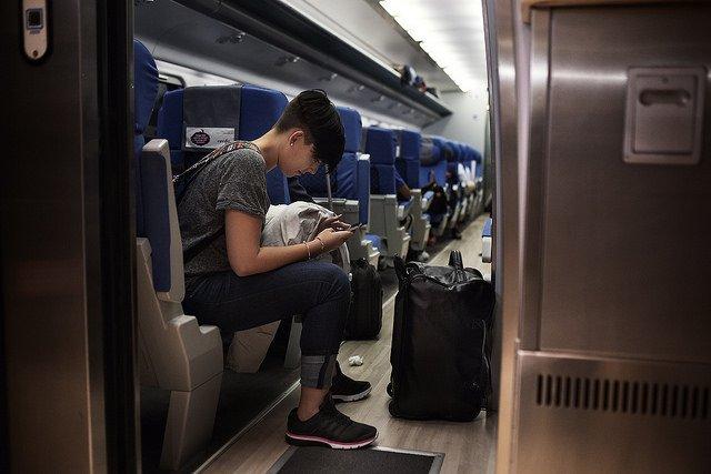 Julia Perez Priego, 23 , Graduada en ADE en la Universidad Loyola de Cordoba, consulta su teléfono camino a Málaga, donde cogerá un vuelo a Irlanda. Foto / GABRIEL PECOT.
